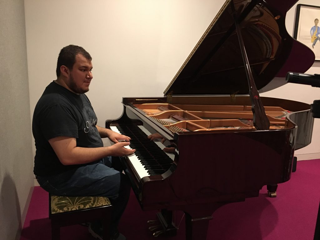 A photograph of Hector Ibarra sitting at a grand piano during a recording session.